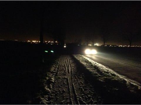 深夜の雪道を走る車