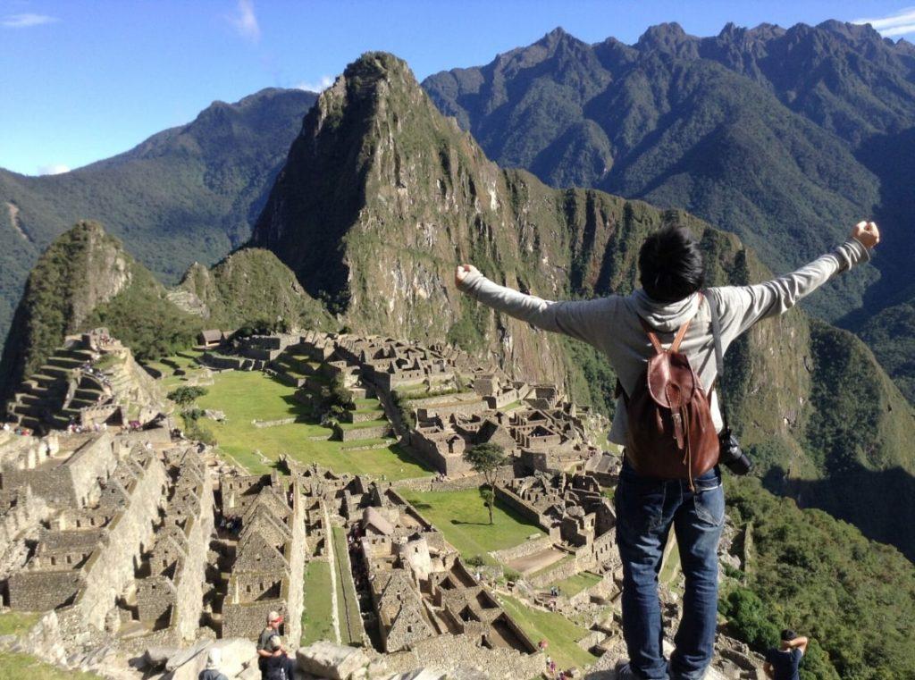 ペルーのマチュピチュ遺跡で両手を広げて記念写真を撮る男性