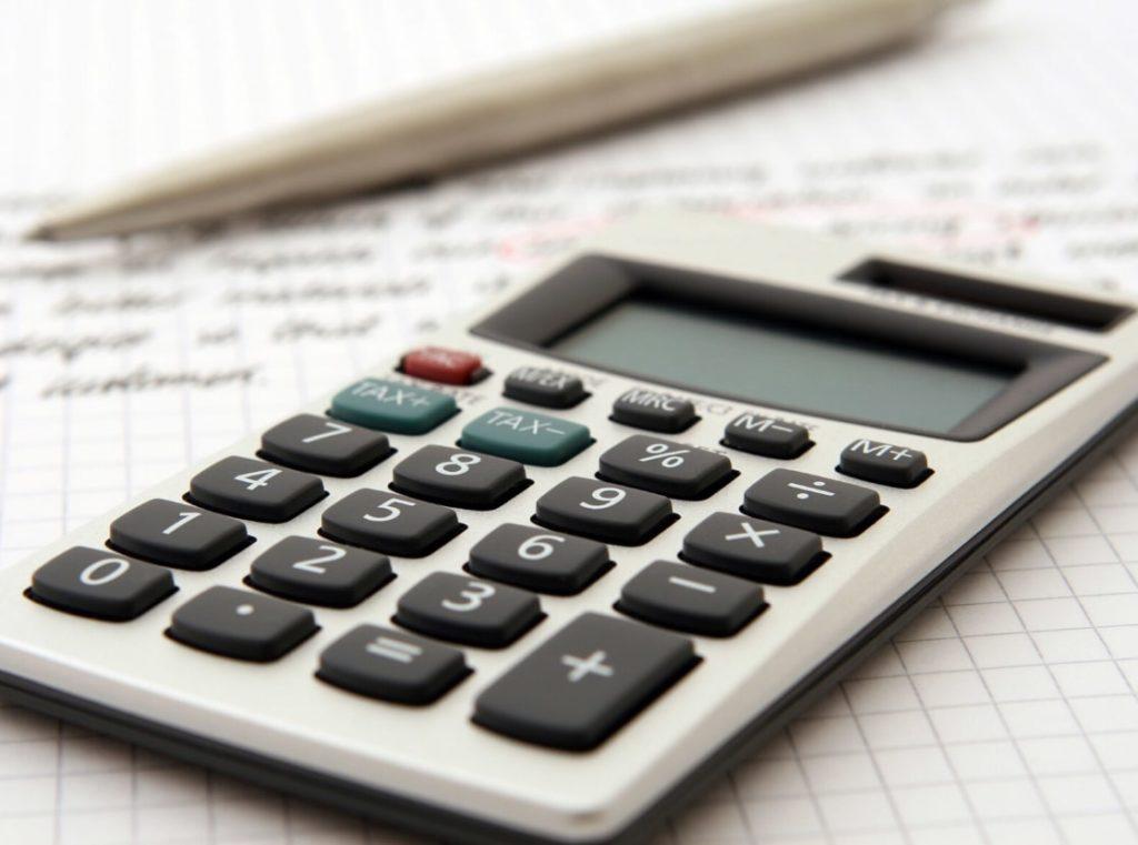 数字とプランが書かれた紙と計算機