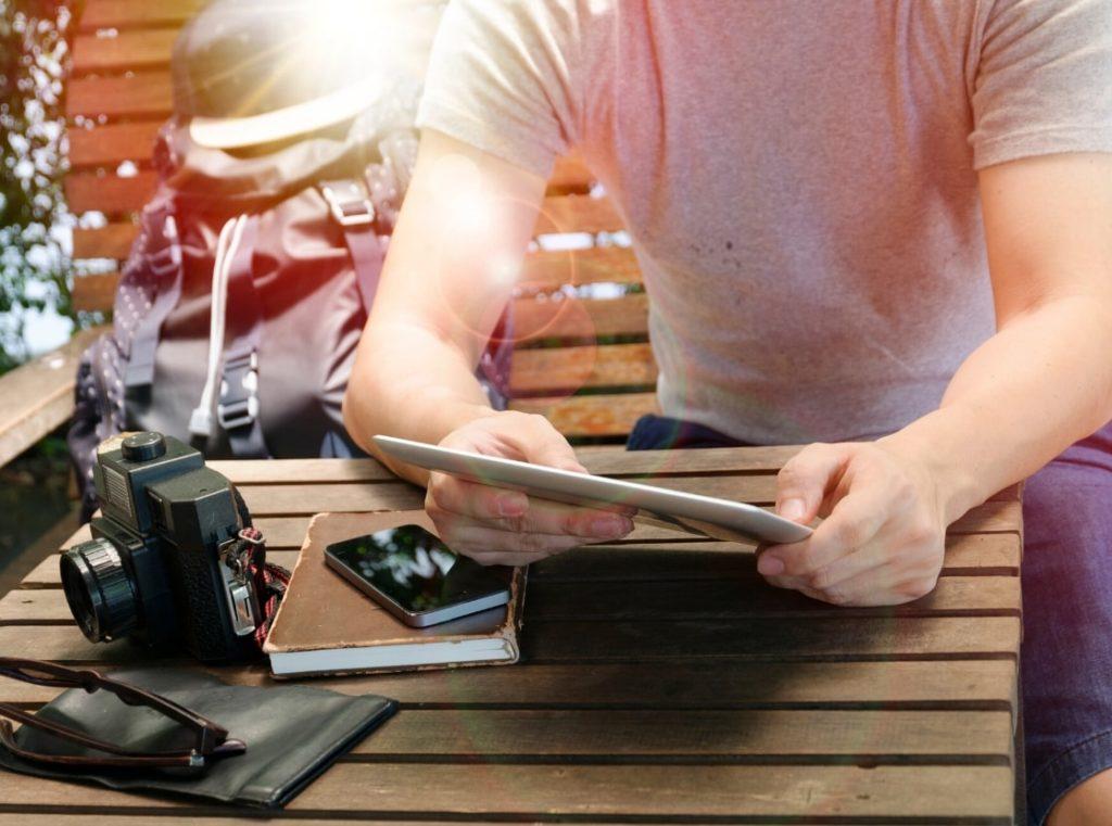 カメラとiPadと手帳と旅行カバンをもつ男性