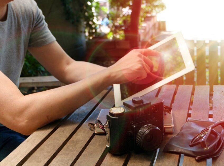 テーブルに置かれたカメラと電子デバイスを持つ男