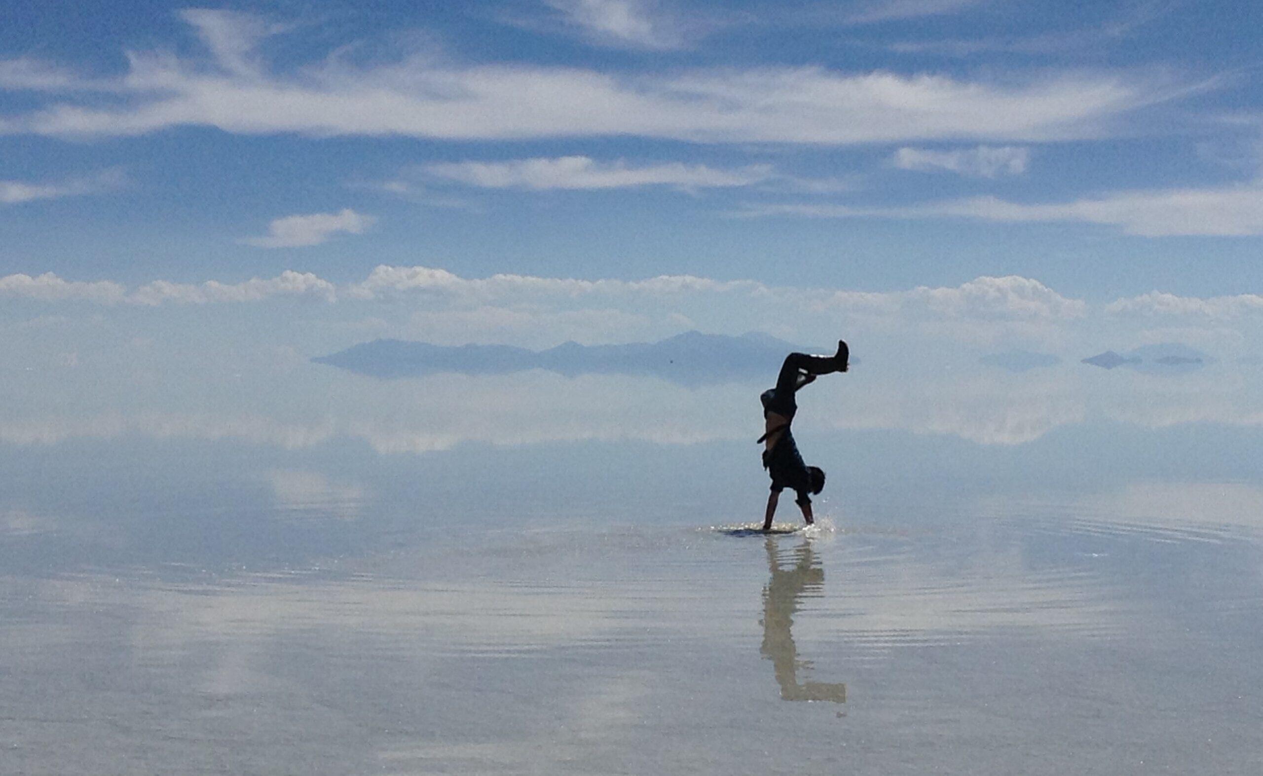 ウユニ塩湖で逆立ちする旅行者