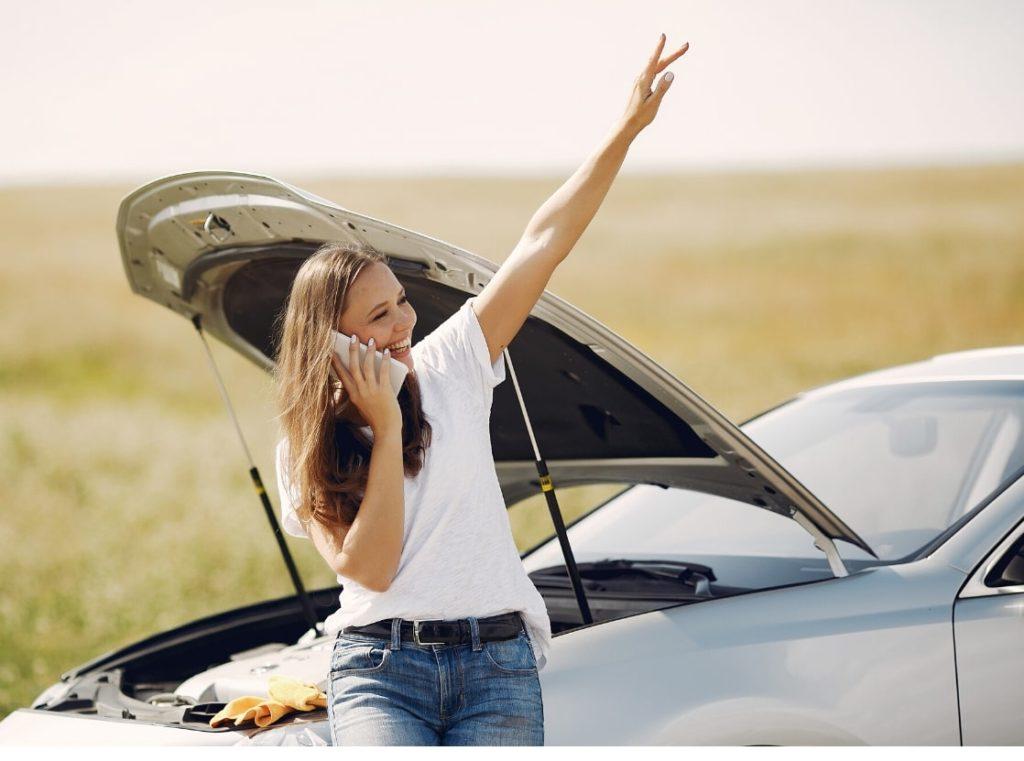 笑顔で手を上げる女性と壊れた車