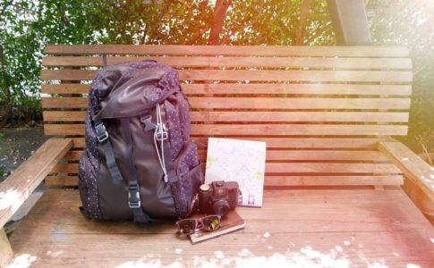 ベンチに置かれた旅行バックとカメラと地図