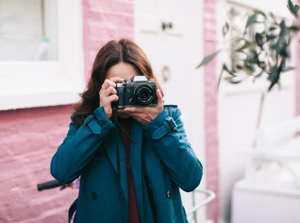 レインコートを着てカメラをかまえる女性