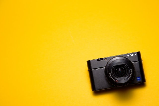 黄色い紙の上に一つおかれたコンデジカメラ