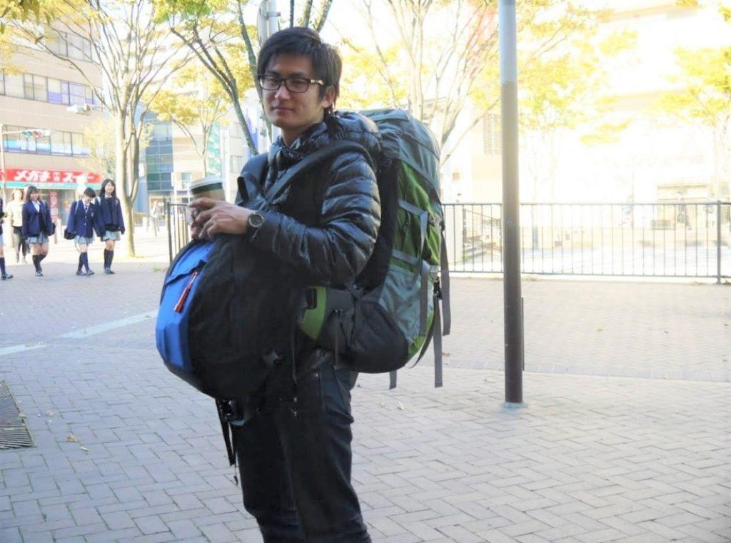 重い旅行カバンを抱える男
