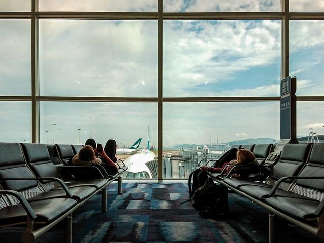空港のベンチで飛行機を待つ旅行者